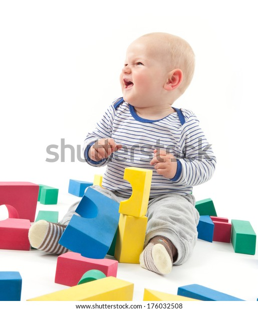 A baby playing with brightly colored wooden blocks.