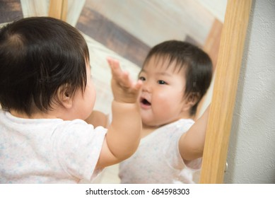 Baby playing by watching the mirror