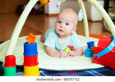 Baby playing with colorful toys at home. Happy 6 months old baby child playing and discovery.