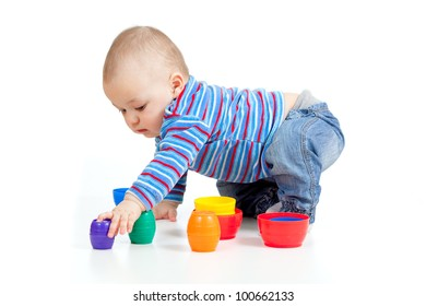 baby playing with colourful cup toys on floor, isolated over white