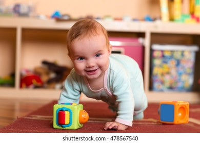 Baby playing and crawling around, making faces, on a rug on the floor.