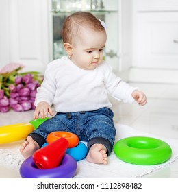 The baby is playing a developing toy. Square. Child under 1 year. The concept of childhood development and lifestyle.