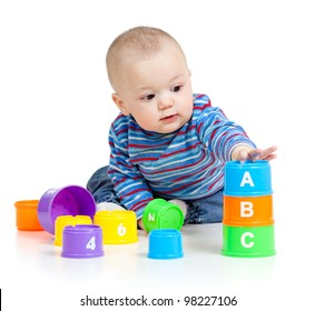 Baby playing with educational cup toys. Isolated on white background