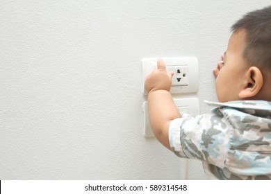 Baby playing with electrical outlet.