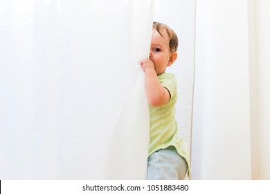 baby playing and hiding with white curtains