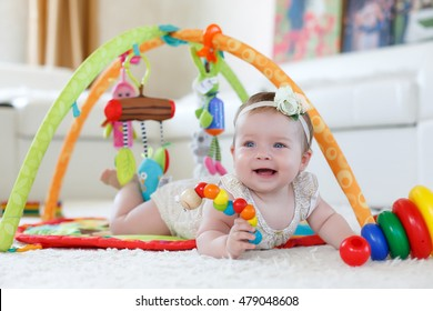 baby playing. little baby playing with toys at home. happy child girl sitting on floor in nursery. 8 months baby girl
