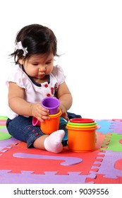 Baby playing on a colorful alphabet mat