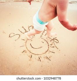 Baby playing on the sandy beach near the sea