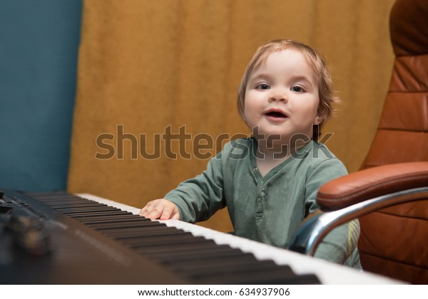 Baby  playing a piano synthesizer. Training of the child in music. Home studio.