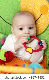 The baby playing with rattle ring at home