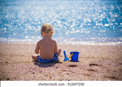 baby playing with sand on sea shore