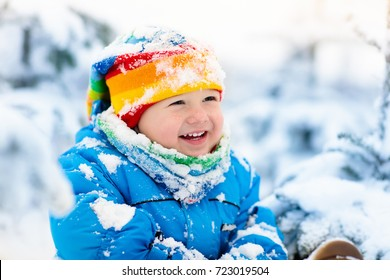 Baby playing with snow in winter. Little toddler boy in blue jacket and colorful hat catching snowflakes in winter park on Christmas. Kids play in snowy forest. Children catch snow flakes