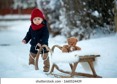 Baby playing with teddy in the snow, winter time. Little toddler boy in blue coat, sliding on sledge, holding teddy bear, playing outdoors in winter park. Children play in snowy park