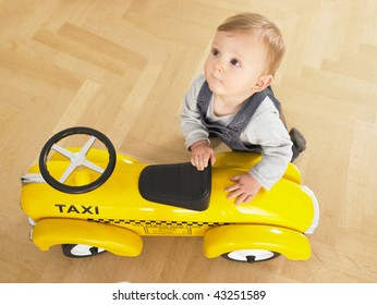 Baby playing with toy taxi cab car. Horizontally framed shot.