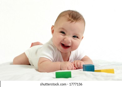 Baby playing with wooden blocks and smiling at the camera.