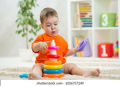 Baby plays sitting on floor. Educational toys for preschool and kindergarten child. Little boy building pyramid toys at home or daycare.