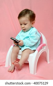 baby with pocket PC sitting on chamber-pot