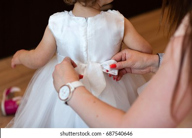 Baby prepared by mother with white ceremonial clothes. Baptism clothes. Christening