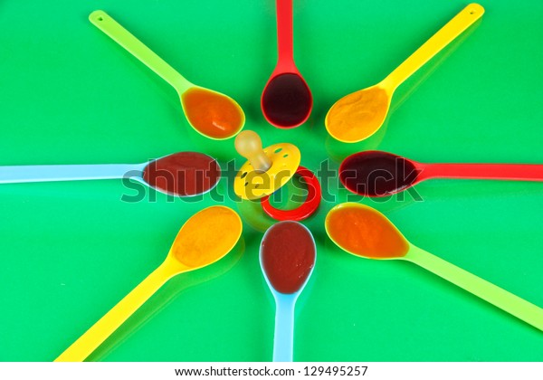 Baby puree in spoons with nipple on green background