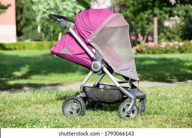 Baby pushchair with mosquito net is on green meadow in summer sunny park, an infant perambulator series