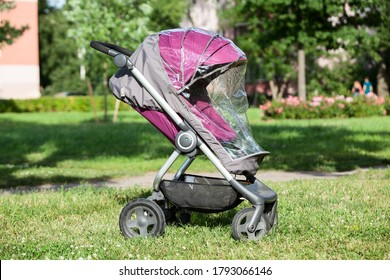 Baby pushchair with rain screen is on green meadow in summer sunny park, infant perambulator series