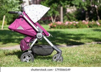 Baby pushchair with summer kit is on green meadow in summer sunny park, infant perambulator series