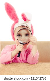Baby rabbit ears sitting at a table looking through a magnifying glass.
