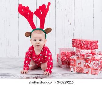 Baby as raindeer sitting next to gifts
