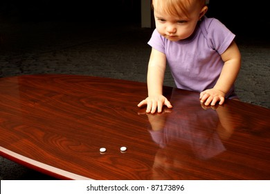 Baby reaching across coffee table at white pills