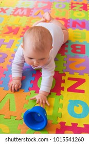 Baby reaching for cup on alphabet mat during tummy time.