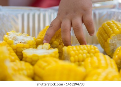 Baby reaching hand to to shiny yellow sweet corn cobs in a plate