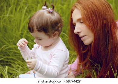 baby and redhead mother outdoor grass playing park together