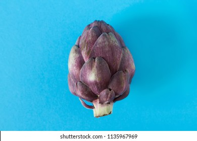 Baby ripping organic Artichokes. Food for a vegan and a vegetarian. Diet, food concept. Multicolored background