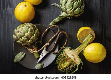 Baby ripping organic Artichokes in the rustic wooden board with lemon, solfetka. Dark background
