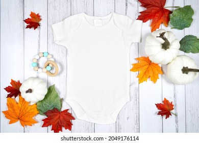 Baby romper jumpsuit onesie product mockup. Thanksgiving farmhouse theme with turkey, white pumpkins and autumn fall leaves, on a white wood background. Negative copy space.