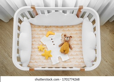 Baby romper with toy bear for a newborn in cot, cradle.  White wooden baby crib with pillows shaped clouds  in baby's room. Top view of child's bed