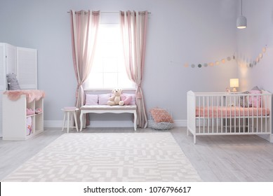Baby room interior with comfortable crib and indoor bench