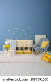 Baby room interior with crib and rocking chair near wall