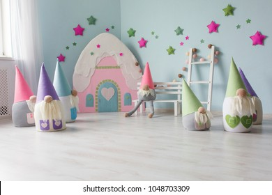 Baby room interior with toy house and textile dwarfs. Light pastel colors