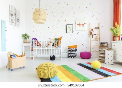 Baby room with white wall and light wooden furniture