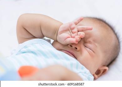 Baby rubbing it's eyes, feeling sleepy.