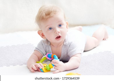 The baby s teeth are being cut. A cute kid with blue eyes is playing with toy