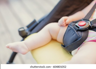 Baby safety protection concept with red button. Newborn baby sleeping in stroller outdoors.