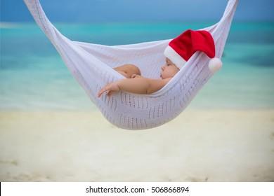 baby Santa in Christmas hat sleeping in hammock over the sea