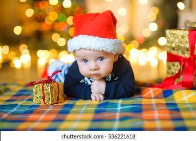baby in Santa Claus's cap, lies on a cover near a gift. With surprise watches in the camera, on a background a set of bright fires, soft focus.