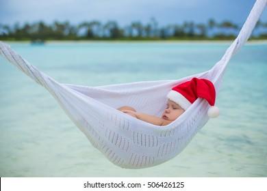 baby Santa sleeping in hammock over the sea