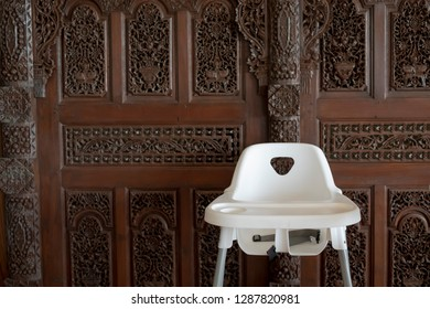 Baby seat in front of Gebyok. Gebyok is one of the typical Javanese furniture in the form of a Javanese space partition that is generally made of teak wood.