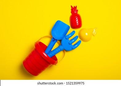 Baby set red sandbox bucket shovel rake toy on yellow background, top view