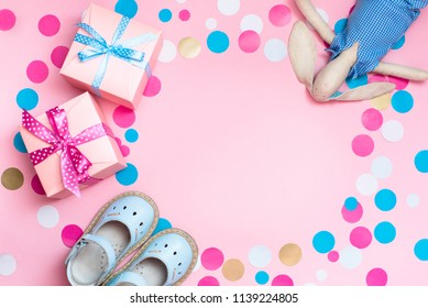 Baby shoes, gift boxes and confetti, on the pink background, as a concept of a children's holiday.