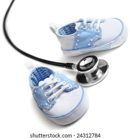 Baby shoes with stethascope against a white background.